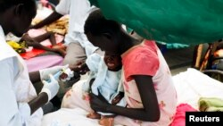 FILE - A medical staff attends to a malnourished child at a Medecins Sans Frontieres hospital in a displaced-persons camp inside the U.N. base in Malakal, South Sudan, July 24, 2014.