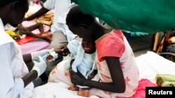FILE - A medical worker attends to a malnourished child at a Medecins Sans Frontieres hospital in a displaced-persons camp inside the U.N. base in Malakal, South Sudan, July 24, 2014.