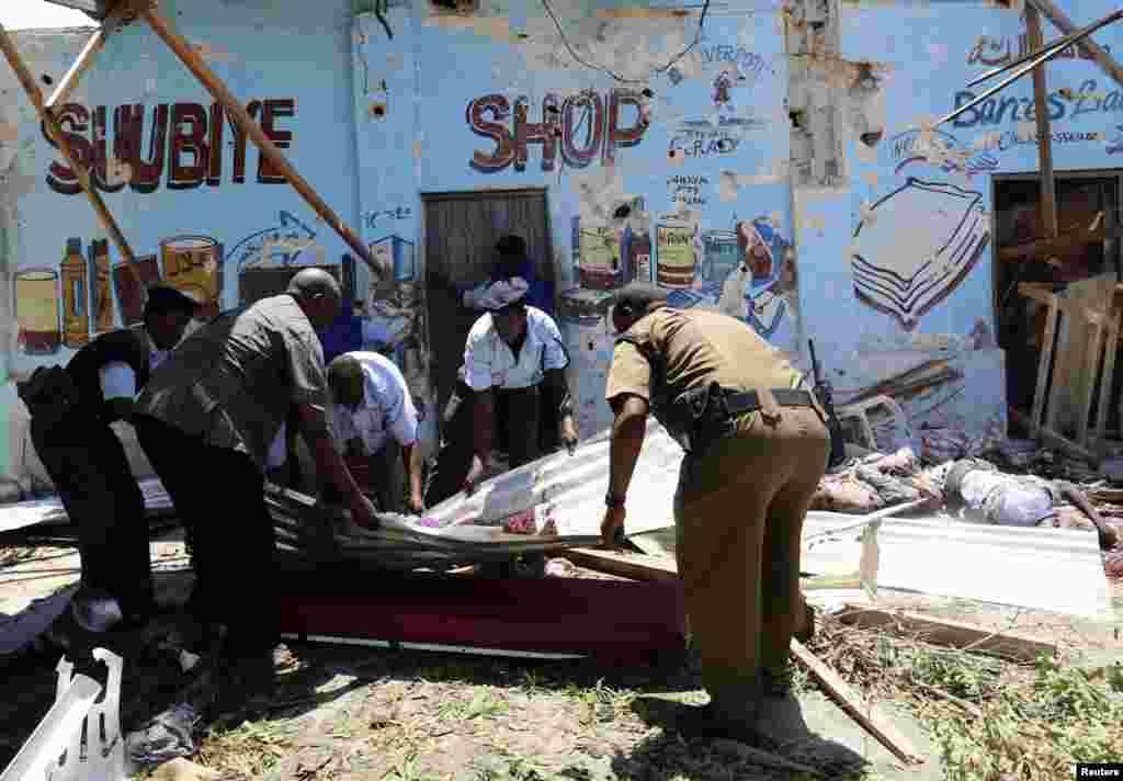 A polícia somali desloca um cadáver no local onde um carro-bomba explodiu junto a um café em Mogadíscio, Somália, Fev. 27, 2014.