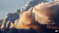 Sekelompok burung terbang saat asap membubung dari kebakaran hutan Fort McMurray di Kinosis, Alberta, Kanada (5/5). (Reuters/Mark Blinch)
