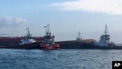 Empat kapal tunda (tug boats) menggerakkan kapal keruk yang sebagian tenggelam ke daerah dekat Pulau Senang, Singapura, dan menindaklanjuti operasi pencarian bawah air, Rabu, 13 September 2017. (Foto: Otoritas Maritim dan Pelabuhan Singapura via AP)