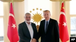 Turkey's President Recep Tayyip Erdogan, right, shakes hands with Hamas movement chief Ismail Haniyeh. (File)