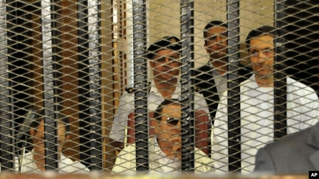Ousted Egyptian president Hosni Mubarak, center, listens to proceedings from inside the defendant cage while flanked by his sons Alaa, left and Gamal, right, in a courtroom in Cairo, July 6, 2013.