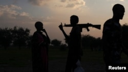 FILE - An armed man and a woman talk in Yuai Uror County, South Sudan, July 24, 2013. Tensions remain high after President Salva Kiir issued a decree last November splitting South Sudan's 10 states into 28, including the newly created states of Terkeka and Jubek.