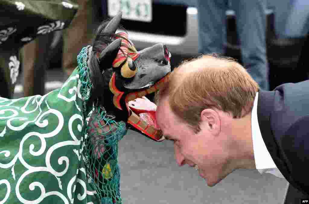 پرنس ويليام بريتانيايی (راست)، دوک کمبريج، در سفرش به ژاپن از يک مرکز خريد در اوناگاوا ديدار به عمل آورد و با يک رقص سنتی مورد استقبال قرار گرفت.