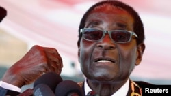 FILE: Zimbabwe's President Robert Mugabe addresses the crowd gathered to commemorate Heroes Day in Harare, Aug. 12, 2013.