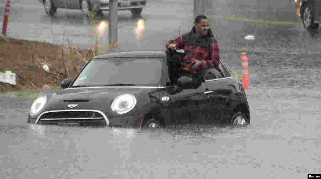 A driver climbs out of a window of his car after driving onto a flooded road in Van Nuys, California, Jan. 5, 2016.