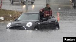 Seorang pengemudi mobil memanjat keluar dari mobilnya yang terjebak banjir di Van Nuys, California, 5 Januari 2016.