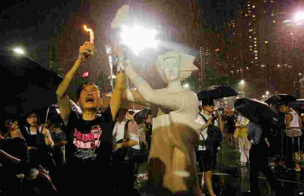 4일 홍콩 빅토리아 광장에서 열린 텐안먼 사태 24주년 촛불집회에서, 민주주의를 상징하는 조각상 옆에서 시위하는 시민.