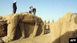 Iraqi workers clean a winged-bull statue at an archeological site in Nimrud. (File)