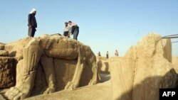 FILE - Iraqi workers clean a winged-bull statue at an archeological site in Nimrud in this 2001 photo. Islamic State militants have bulldozed and plundered the ancient site, Iraq's government says, March 6, 2015.