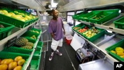 Jock Riggins looks over the fresh fruits and vegetables on the Fresh Stop bus, a mobile market, in Eatonville, Florida, July 15, 2015.
