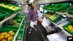 FILE - Jock Riggins looks over the fresh fruits and vegetables on the Fresh Stop bus, a mobile market, in Eatonville, Florida, Jul. 15, 2015. Under proposed rules retailers that accept food stamps would have to stock a wider variety of healthy foods.