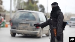 Similar to female fighters who run checkpoints for forces of Bashar al Assad in Damascus, a female member of the Al-Ikhlas [Loyalty] Battalion stops a van at a rebel checkpoint, Aleppo, March 31, 2013.