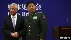 U.S. Secretary of Defense Chuck Hagel (L) shakes hands with Chinese Minister of Defense Chang Wanquan in Beijing April 8, 2014.