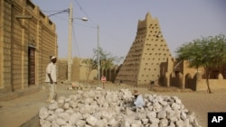 Men work alongside one of Timburktu's historic mud mosques, in Timbuktu, Mali. (file photo)
