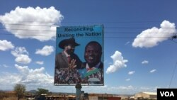 A billboard in South Sudan's capital Juba on April 15, 2016 shows South Sudan's President Salva Kiir (L), and rebel leader Riek Machar (R), who is scheduled to return to the city and assume the vice presidency on Monday. (VOA/J. Patinkin)