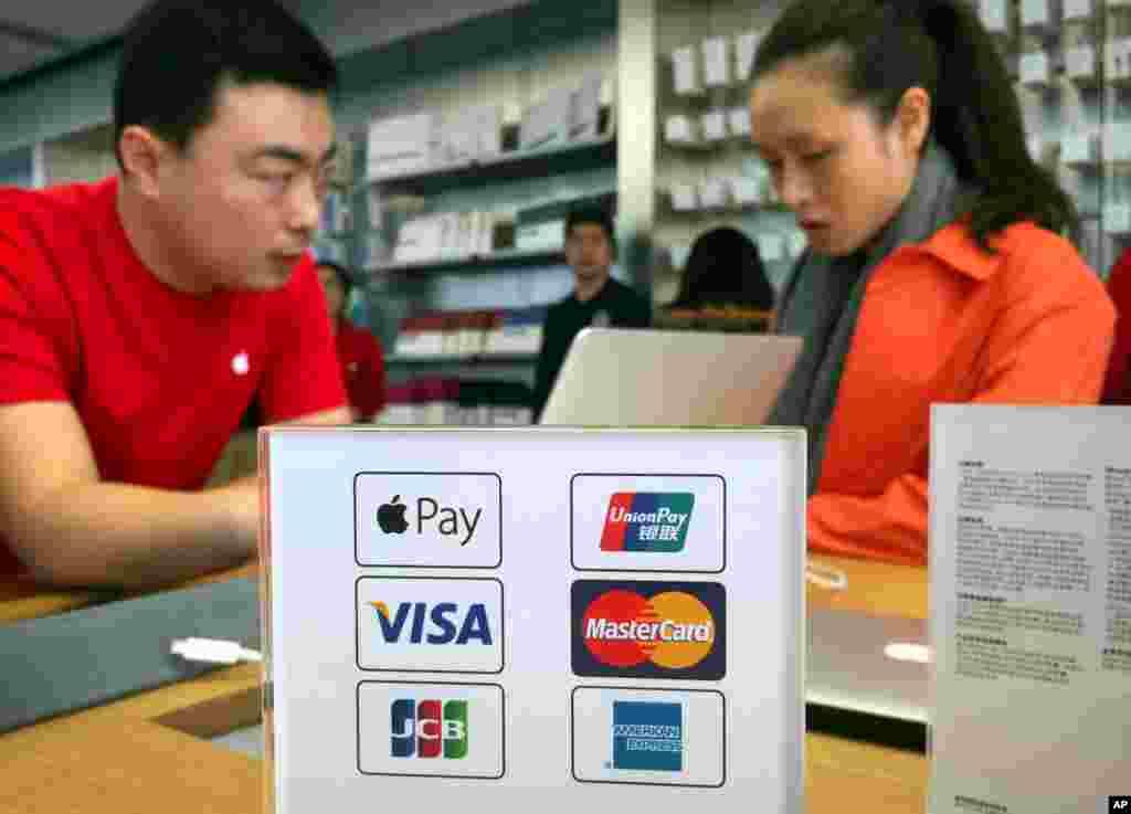 """2016年2月18日北京一家苹果店里的职工和顾客,旁边有各种付款方法的标志,包括刚刚进入中国市场的苹果公司移动支付系统""""苹果支付""""(ApplePay)。。中国是亚洲第一个苹果支付上线的国家。苹果同中国银联合作参与中国市场。这能让苹果公司成为中国巨大移动支付市场的一个主要参与者,与另外两个中国国内支付品牌阿里巴巴公司的支付宝以及腾讯的社交平台微信支付(微信钱包)竞争。"""