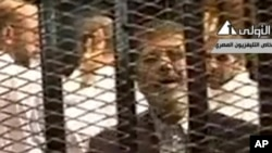 FILE - Video broadcast on Egyptian State Television shows ousted President Mohammed Morsi speaking from inside a mesh cage as he stands with other defendants during a court hearing at a police academy compound in Cairo, Egypt.