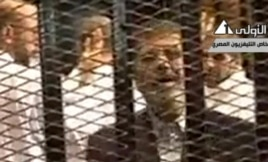 Video broadcast on Egyptian State Television shows ousted President Mohammed Morsi speaking from inside a mesh cage as he stands with other defendants during a court hearing at a police academy compound in Cairo, Egypt, Nov. 4, 2013.