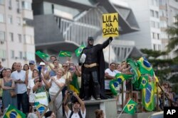 "A demonstrator dressed as Batman holds a sign that reads in Portuguese ""Lula in Prison"" during a protest against former President Luiz Inacio Lula da Silva on Copacabana beach, in Rio de Janeiro, Brazil, Jan. 23, 2018."