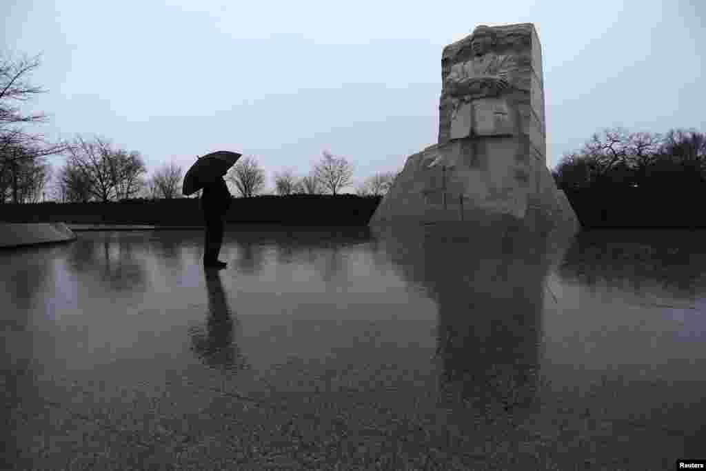 Di bawah payung dan hujan yang tak kunjung henti, seorang warga AS memberi penghormatan di Memorial Martin Luther King, Jr. di Washington (18/1). (Reuters/Jonathan Ernst)