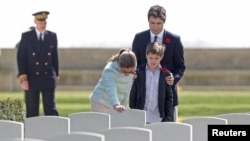 Canadian Prime Minister Justin Trudeau, his wife Sophie Gregoire and son Xavier pay their respects at the tombstone of J.R. Gregoire, an ancestor who died during fighting in WWII, during their visit to the Canadian War Cemetery in Beny-sur-Mer, France, April 10, 2017.