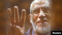 FILE - The Brotherhood's Supreme Guide Mohamed Badie waves with the Rabaa sign, symbolizing the support of the Muslim Brotherhood, as he stands behind bars during his trial with ousted Egyptian president Mohamed Morsi and other leaders of the Muslim Broth