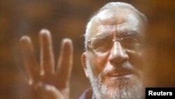 Muhammed Badie geçen Kasım ayında çıkarıldığı duruşmada tutulduğu sanık kafesi ardından selam verirken