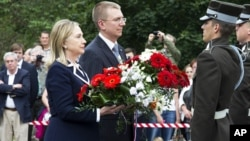 U.S. Secretary of State Hillary Rodham Clinton pays her respects at the Freedom Monument with Latvian Foreign Minister Edgar Rinkevics in Riga, Latvia, June 28, 2012.