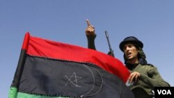 Yon rebèl k ap fè jès kot drapo libyen an sou tèt yon machin nan lès Brega 4 avril 2011