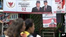 A couple rides a motorcycle past a campaign banners for Indonesian presidential candidate Prabowo Subianto, left, and running mate Sandiaga Uno in Jakarta, Indonesia, Jan. 17, 2019. (AP Photo/Achmad Ibrahim)