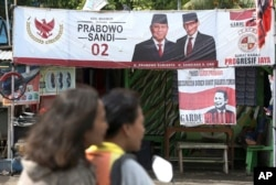 FILE - A couple rides a motorcycle past a campaign banners for Indonesian presidential candidate Prabowo Subianto, left, and his running mate Sandiaga Uno in Jakarta, Indonesia, Jan. 17, 2019.