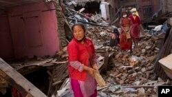Warga berusaha mencari barang-barang di antara reruntuhan rumahnya akibat gempa di Bhaktapur, Nepal (3/5). (AP/Bernat Amangue)