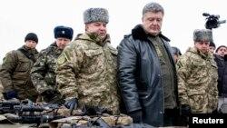 Ukrainian President Petro Poroshenko (2nd R) inspects military hardware as he visits the Yavoriv military range outside Lviv, western Ukraine, Dec. 30, 2014.