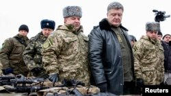 Ukrainian President Petro Poroshenko (2nd R) inspects military hardware as he visits the Yavoriv military range outside Lviv, western Ukraine, Dec. 30, 2014.