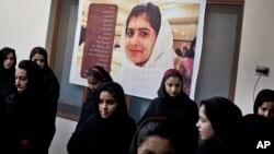 Anak-anak perempuan Pakistan berada di sekolah dengan poster teman sekelas mereka yang ditembak militan Taliban, Malala Yousafzai di sekolah Khushal kota Mingora, Lembah Swat, Pakistan (foto: dok).