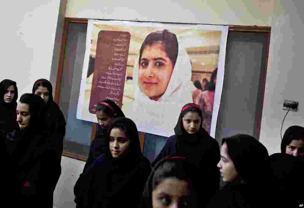 Pakistani school children gather under a poster of injured classmate Malala Yousafzai at the Khushal School for Girls, as they wait to be collected before classes in Mingora, Swat Valley, Pakistan, November 15, 2012.