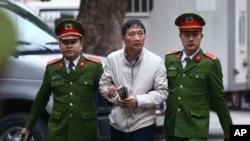 Trịnh Xuân Thanh (giữa) bị cảnh sát dẫn ra tòa ở Hà Nội hôm 24/1/2018 và sau đó bị kết 2 án chung thân vì tội làm trái quy định.