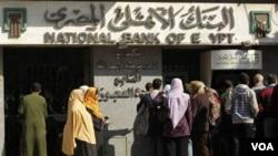 Warga di Mesir mengantri untuk mengambil uang dari bank. Bank-bank di Kairo buka selama beberapa jam, Minggu (2/5).