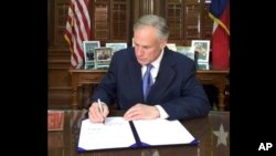 """In this frame from video posted by the Office of the Governor, Republican Gov. Greg Abbott signs a so-called """"sanctuary cities"""" ban in Austin Texas, May 7, 2017."""