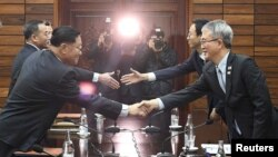 Kwon Hyok Bong, Direktur Biro Seni dan Pertunjukan, Kementerian Kebudayaan Korea Utara berjabat tangan dengan Lee Woo-sung, Ketua Delegasi Korea Selatan, setelah pertemuan di desa gencatan senjata, Panmunjom, Korea Utara, 15 Januari 2018.