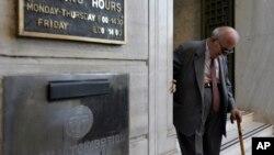 一名希腊老人走出雅典的希腊国家银行分支的大门。(2015年7月20日)