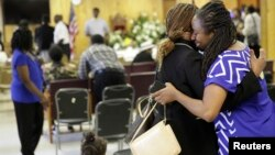 FILE - Waltrina Middleton (R), cousin of shooting victim DePayne Doctor, embraces Claudia Lawton in the basement where a mass shooting occurred at the Emanuel A.M.E. Church four days earlier, in Charleston, South Carolina, June 21, 2015.