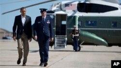 """Presiden Barack Obama didampingi Kolonel Greg Urtso menuju pesawat kepresidenan """"Air Force One"""" di pangkalan Angkatan Udara AS - Andrew di Maryland (26/5). Presiden Obam bertolak ke kota Moore, Oklahoma, untuk mengunjungi korban tornado hari ini."""