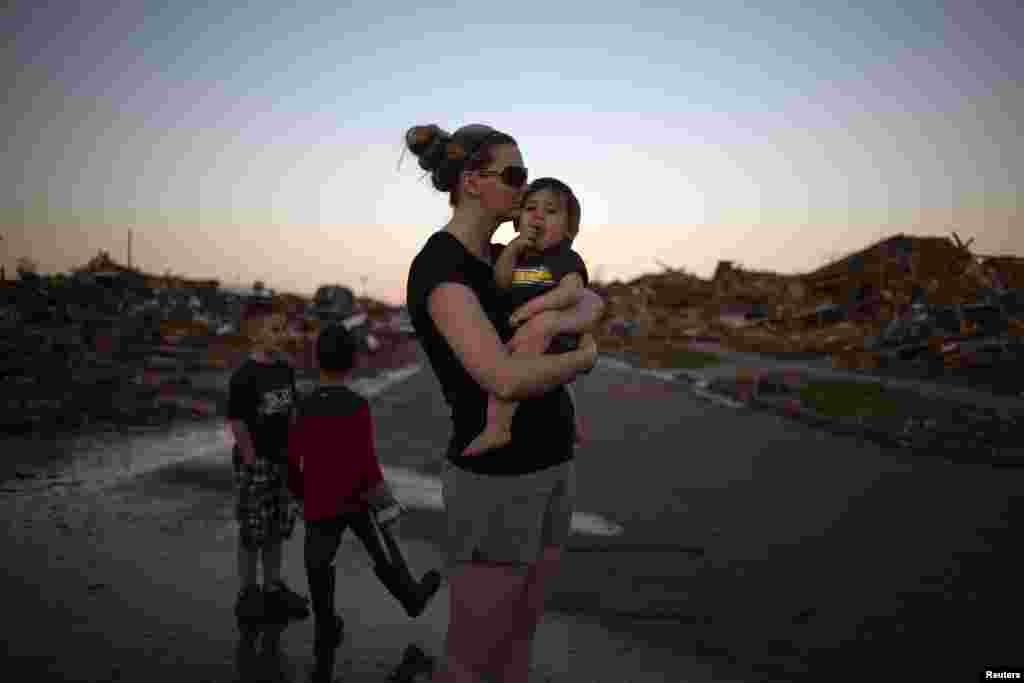 Rae Kittrell holds her son Rylan, who turned one-year-old two days after the tornado, a block away from her house in Moore, Oklahoma, May 22, 2013.