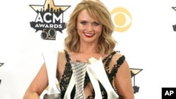 """Miranda Lambert poses in the press room with the milestone award and the awards for song of the year for """"Automatic"""", album of the year for """"Platinum"""" and female vocalist of the year at the 50th annual Academy of Country Music Awards at AT&T Stadium, April 19, 2015, in Arlington, Texas."""