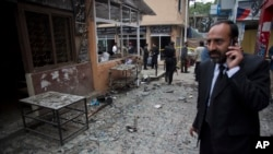 A lawyer talks on his mobile phone at the site of a suicide attack in a court complex, Islamabad, March 3, 2014.