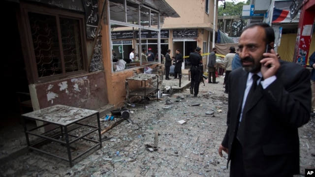 FILE - A lawyer talks on his mobile phone at the site of a suicide attack in a court complex, Islamabad, March 3, 2014.