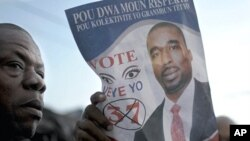 A supporter of Haitian lawmaker Deputy Arnel Belizaire holds up a poster while waiting outside the Toussaint Louverture International Airport where Belizaire was detained by Haitian police in Port-au-Prince October 27, 2011.
